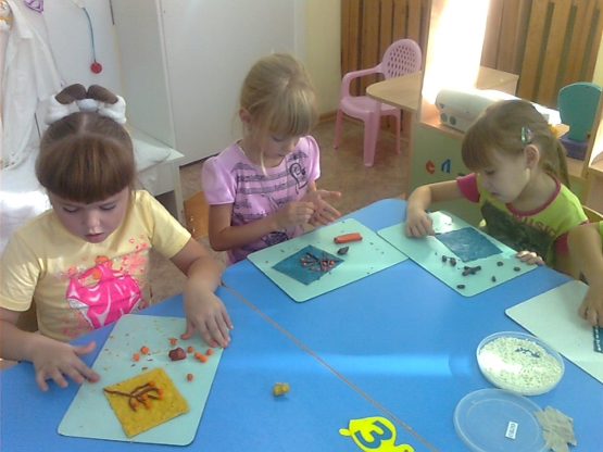 Три девочки рисуют пластилином