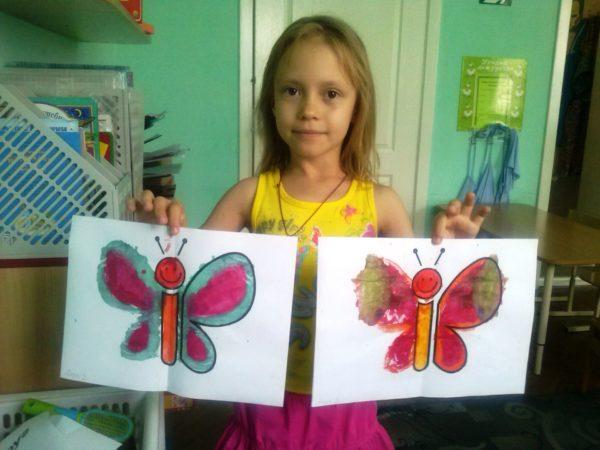Девочка показывает рисунки в технике монотипия