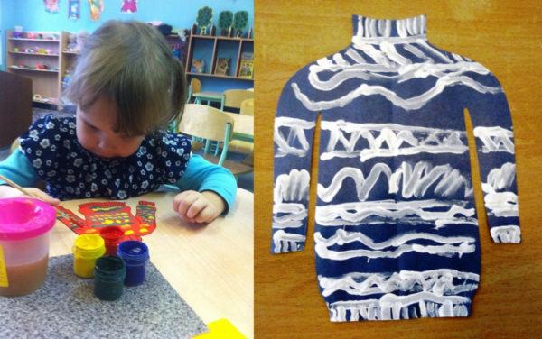 Девочка расписывает шаблон свитера гуашью; синий шаблон, украшенный белой гуашью