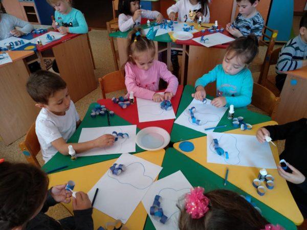 Дети за столом делают аппликацию