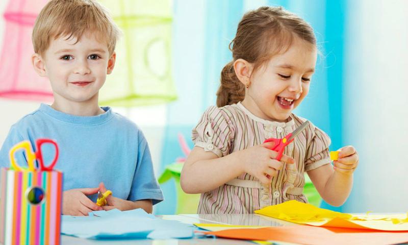 Мальчик и девочка вырезают из бумаги