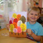 Мальчик держит аппликацию с деревьями