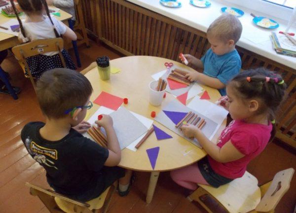 Дети наклеивают на основу бумажные брёвнышки