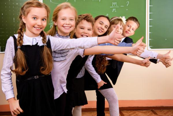 Дети стоят, подняв большие пальцы рук вверх