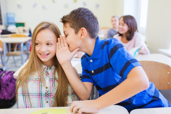 Мальчик шепчет что-то девочке на ухо