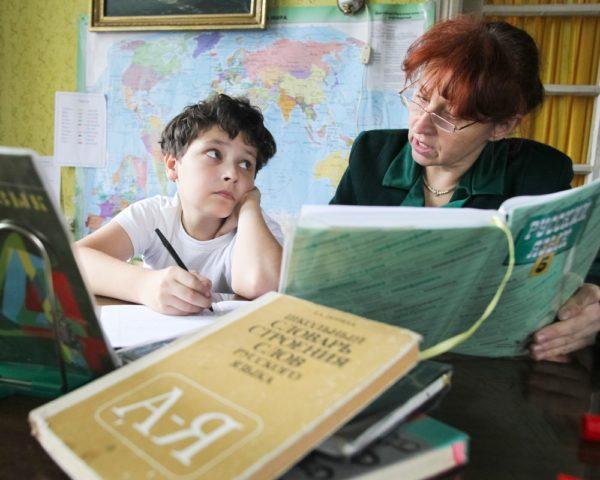 Мальчик и учительница занимаются русским языком