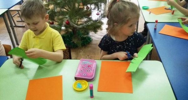 Мальчик и девочка за столом вырезают из бумаги