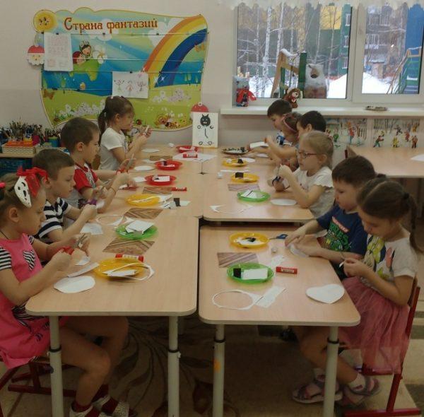 Дети за столами выполняют аппликацию