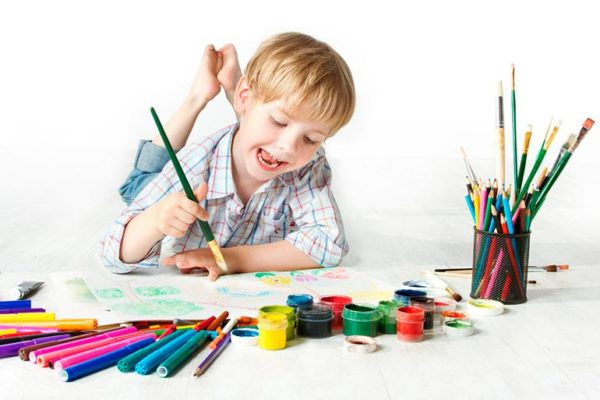 Мальчик рисует кисточкой