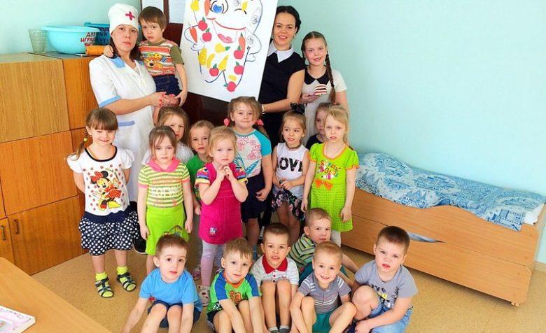 Окружённый детьми педагог держит аппликацию Полезные овощи и фрукты для зубов