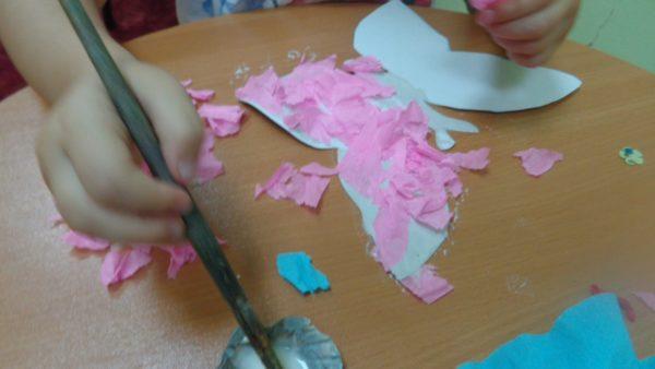 Ребёнок приклеивает кусочки бумаги на шаблон бабочки
