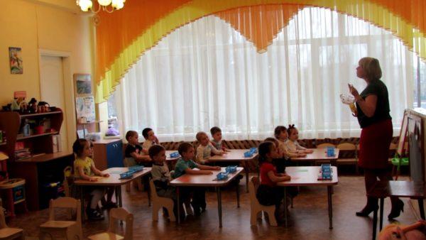 Педагог показывает детям материалы для поделки, сидящим за столами