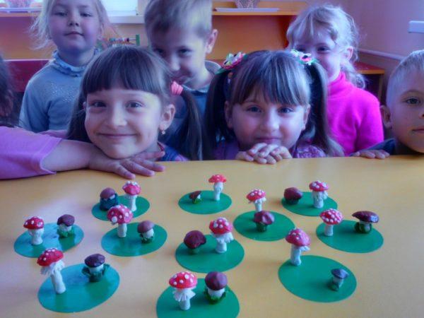 Дети смотрят на поделки — грибы из пластилина