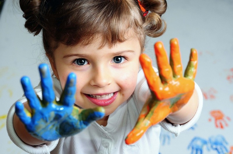 У девочки ладошки в голубой и оранжевой краске