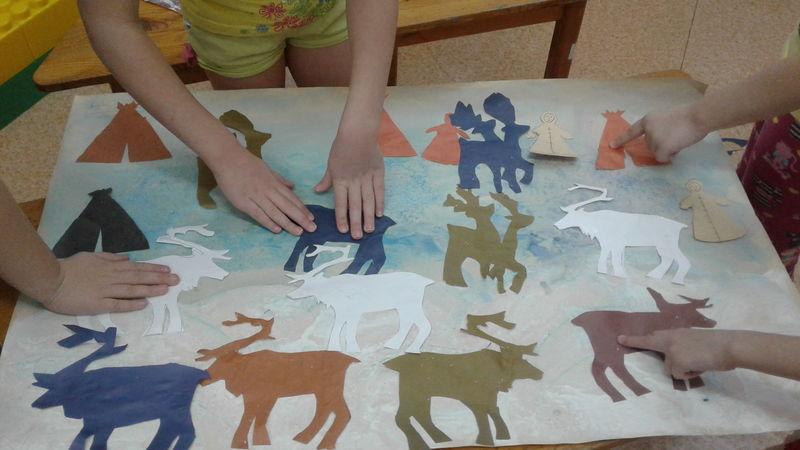 Дети наклеивают на лист ватмана бумажные фигурки лосей