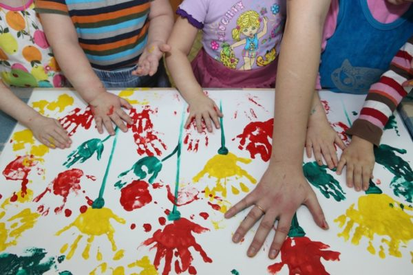 Дети и педагог рисуют на ватмане ладошками
