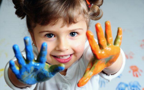 Ладошки девочки окрашены голубым и оранжевым цветом