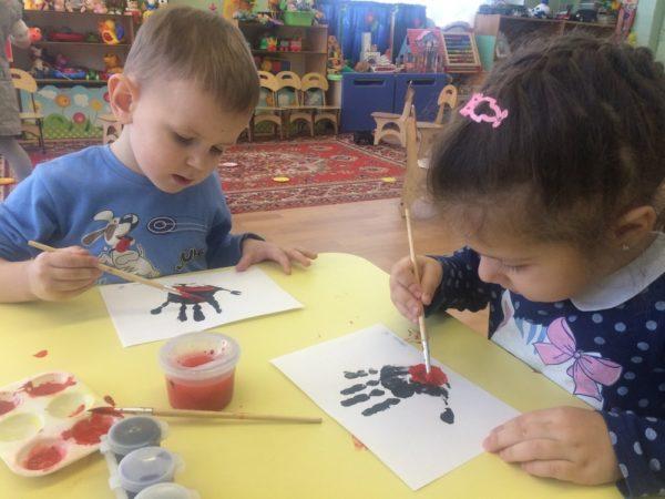 Дети дорисовывают чёрный отпечаток ладошки