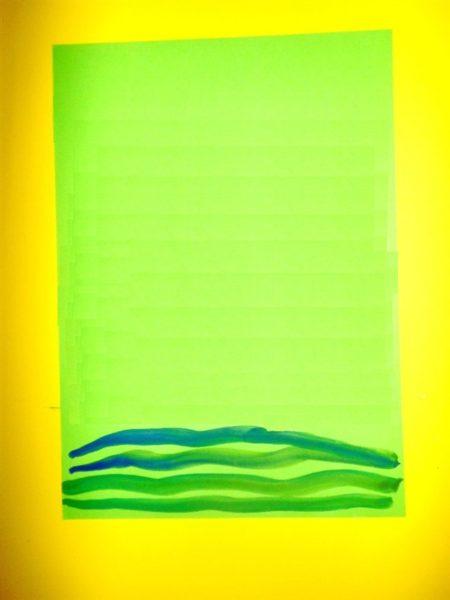 На зелёном листе бумаги ребёнок кисточкой рисует дорожку