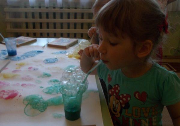 Девочка держит во рту трубочку с подкрашенными мыльными пузырями