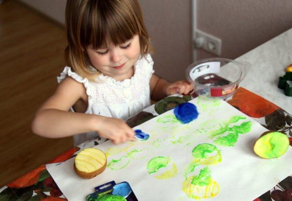 Девочка печатает изображение с помощью штампов из картофеля