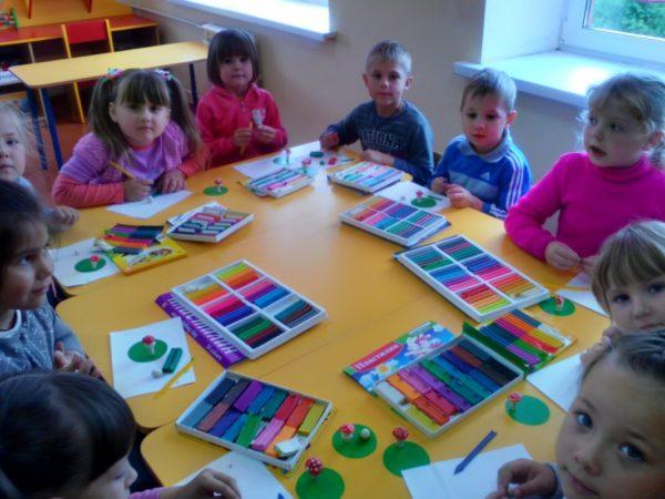 Дети сидят за столом и работают с пластилином