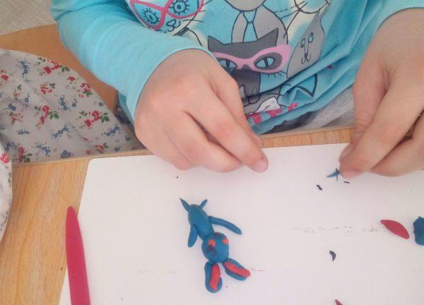 Ребёнок лепит синего зайца