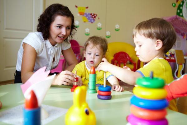 Воспитатель собирает с детьми пирамидки