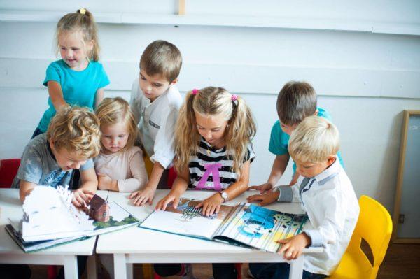 Дети за столом рассматривают книги