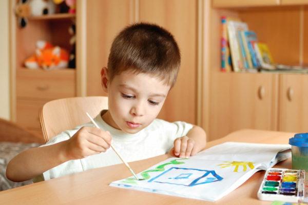 Мальчик рисует домик красками