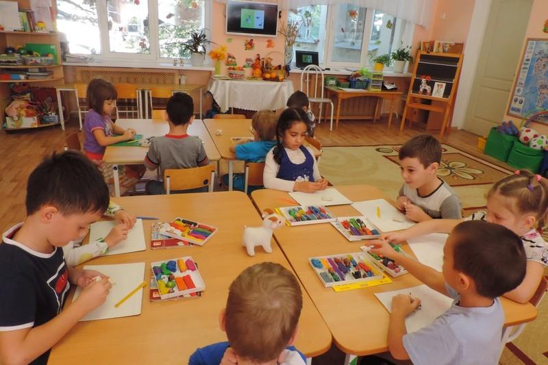 Дети по группам сидят за столами и лепят из пластилина