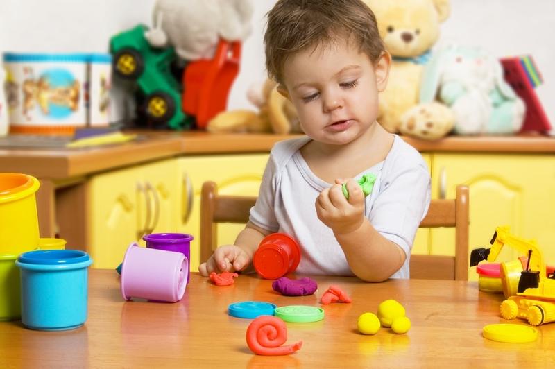 Мальчик сжимает кусок пластилина