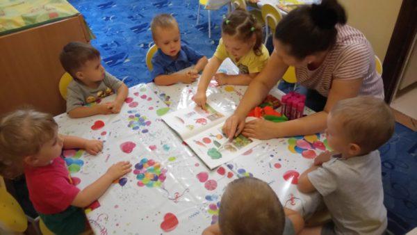 Педагог показывает детям картинки в книге