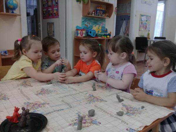 Дети лепят фигурки из серого пластилина