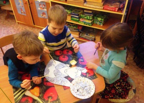 Трое дошкольников совместно выполняют обрывную аппликацию