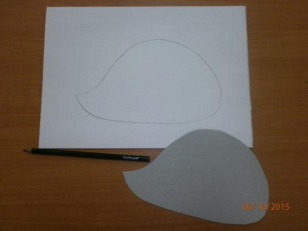 На листе бумаги нарисован силуэт ёжика, рядом лежит шаблон