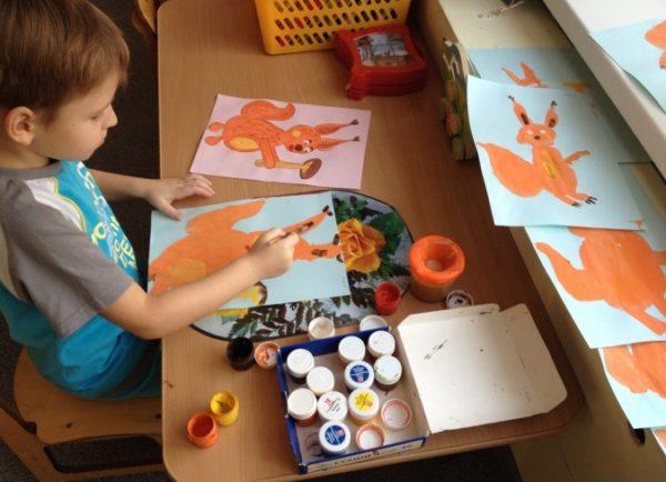 Мальчик рисует гуашью