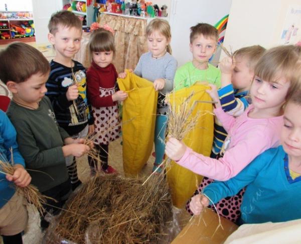 Дети набивают тканевые мешки соломой