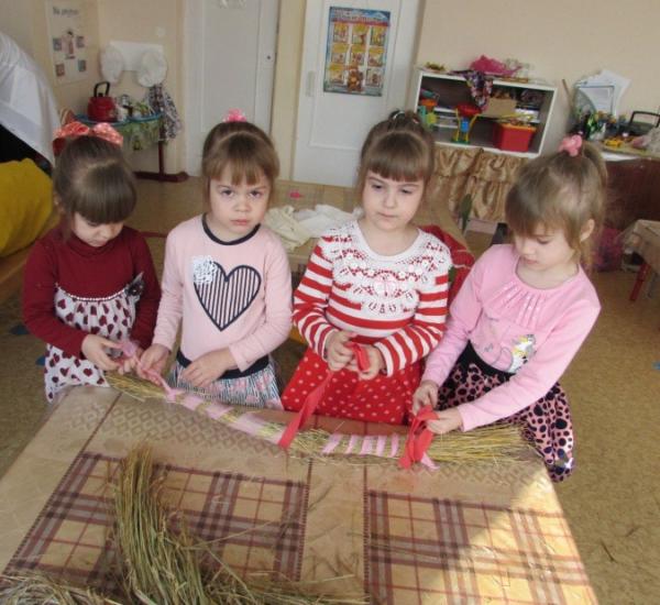 Девочки стягивают пучок соломы лентами