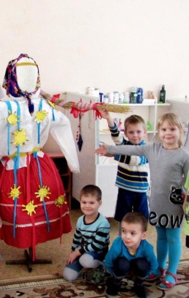 Дети стоят возле чучела Масленицы, украшенного лентами и солнышками