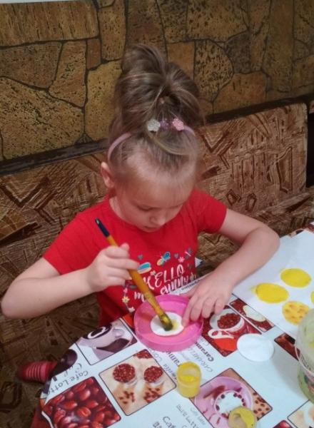 Девочка раскрашивает ватные диски жёлтой краской