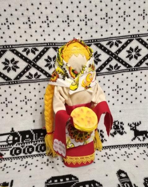 Кукла-масленица держит на рушнике блины