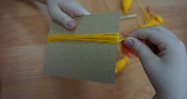 Ребёнок наматывает жёлтую пряжу на картон