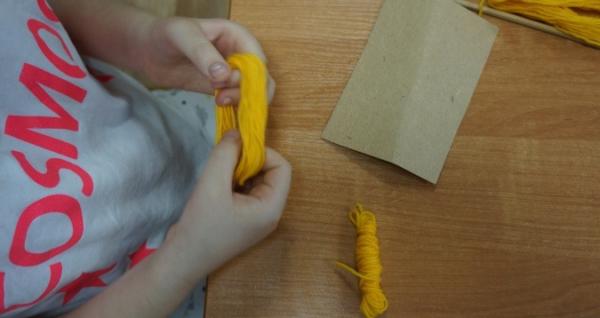 Ребёнок держит в руках моточек жёлтой пряжи