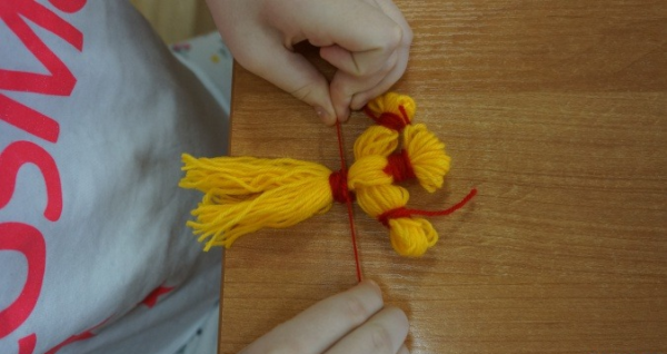 Ребёнок затягивает талию куклы красной ниткой