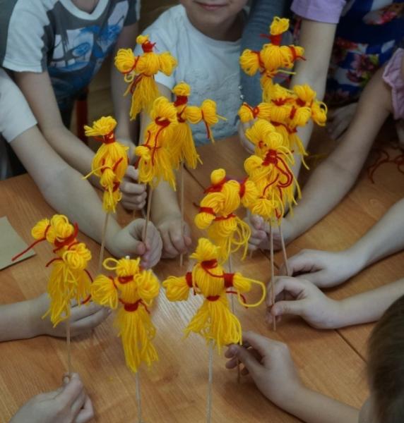 Дети держат несколько кукол-Маслениц из ниток