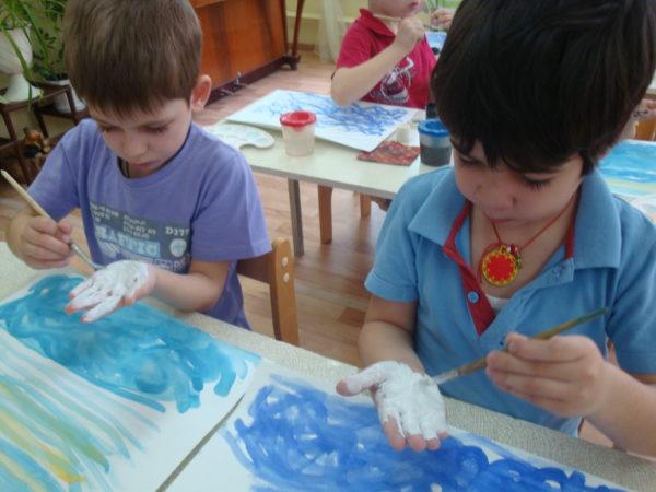 Мальчики наносят краску на ладошки
