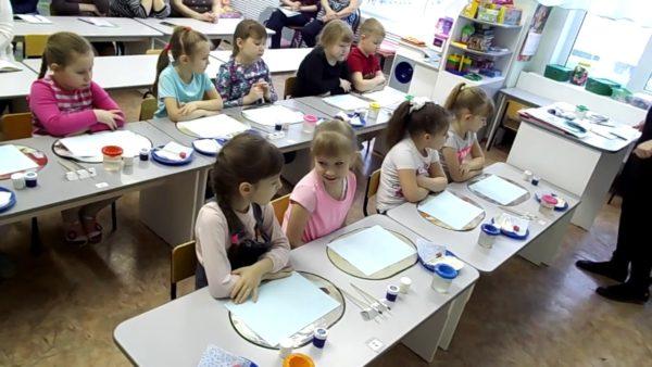 Дети сидят за столами с материалами для рисования