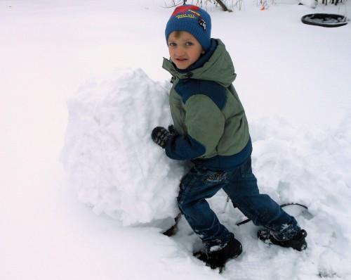 Мальчик катит большой снежный шар