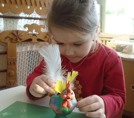 Девочка украшает птицу пером